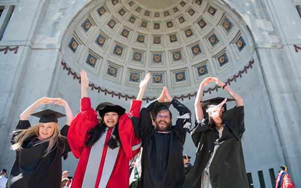 Students in graduate clothing doing O-H-I-O