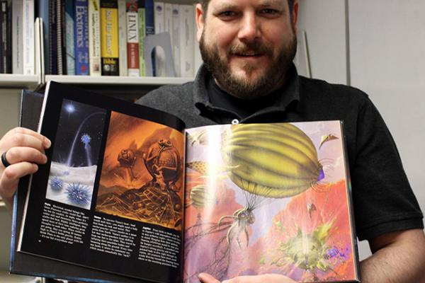 Photo of Professor Scott Guadi holding the book that inspired his interest in astronomy.